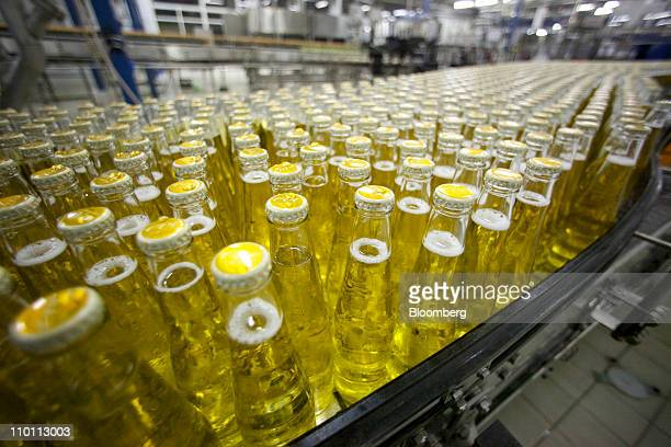 Bottles of Eve soft drinks pass along a conveyor belt at OAO Baltika Breweries Russia's largest beer maker in St Petersburg Russia on Monday March 14...