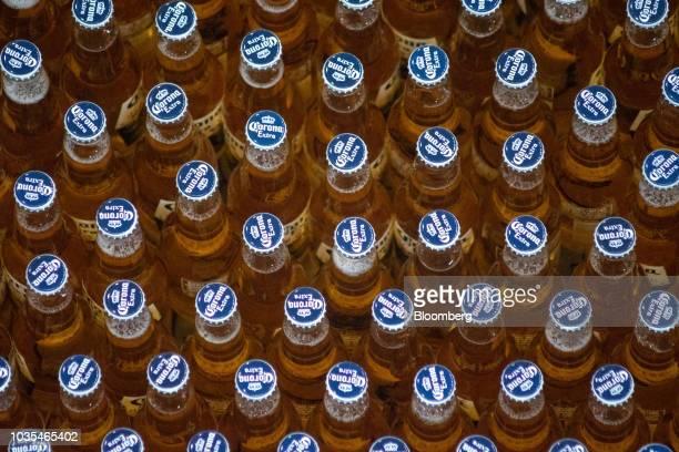 Bottles of Grupo Modelo SAB Corona brand beer move along a conveyor at the Cerveceria Yucateca AnheuserBusch InBev SA facility in Merida Mexico on...