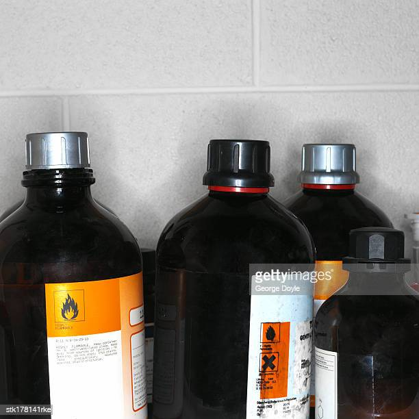bottles of hazardous chemicals - flammable stock photos and pictures