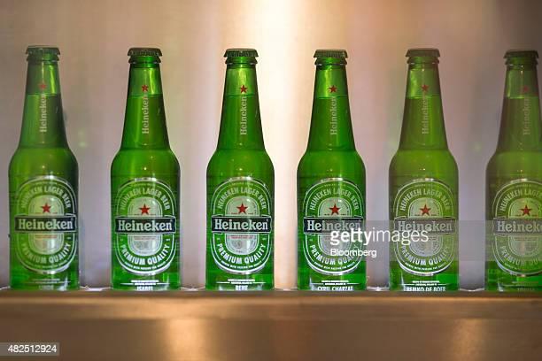 Bottles of Heineken lager beer sit on display in the Heineken NV Experience bar in Amsterdam Netherlands on Friday July 31 2015 Heineken increased...