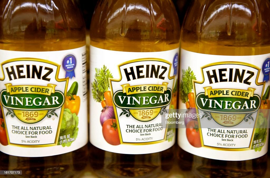 Bottles of H.J. Heinz Co. apple cider vinegar are displayed on a shelf for sale at grocery store in Pittsburgh, Pennsylvania, U.S., on Thursday, Feb. 14, 2013. Warren Buffett's Berkshire Hathaway Inc. and Jorge Paulo Lemann's 3G Capital agreed to buy HJ Heinz Co. for about $23 billion, ending the independence of an iconic ketchup maker that traces its roots to the 1860s. Photographer: Kevin Lorenzi/Bloomberg via Getty Images