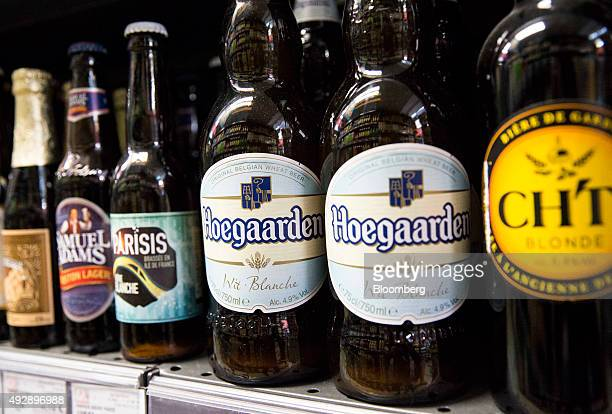 Bottles of Hoegaarden white beer produced by AnheuserBusch InBev NV sit on a shelf with other lagers and ales in a store in Paris France on Thursday...