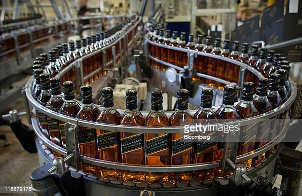 Bottles of Johnnie Walker Black Label whisky pass along the production line at Diageo Plc's Shieldhall factory in Glasgow Scotland on Monday July 11...