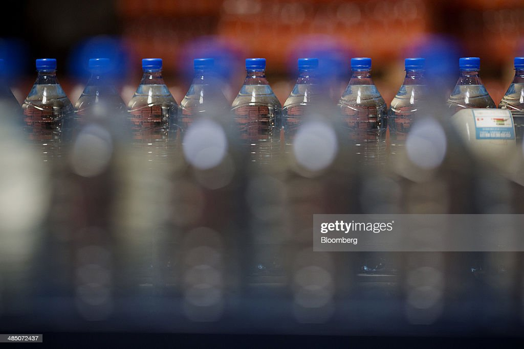 Bottles of Kinley water move along a conveyor belt at the Habib Gulzar Non-Alcoholic Beverage Ltd. bottling facility, a bottler for Coca-Cola Co., in Kabul, Afghanistan, on Thursday, April 10, 2014. Coca-Cola Co., the world's largest soda maker, today showed signs of a rebound in the first three months of the year, easing the concerns that arose when the company unsettled investors with surprisingly sluggish global sales in the fourth quarter. Photographer: Victor J. Blue/Bloomberg via Getty Images