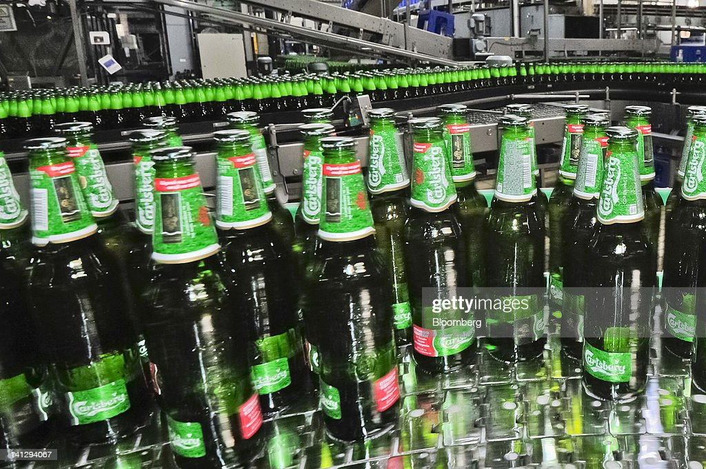 Bottles of lager move along a conveyor belt at the Carlsberg A/S production plant in Kiev, Ukraine, on Wednesday, March 14, 2012. Sales in the Ukraine were 'significantly higher,' helped by better economic conditions and the recent introduction of premium beers, while the U.K. saw 'continuing strong growth,' the brewer said. Photographer: Vincent Mundy/Bloomberg via Getty Images