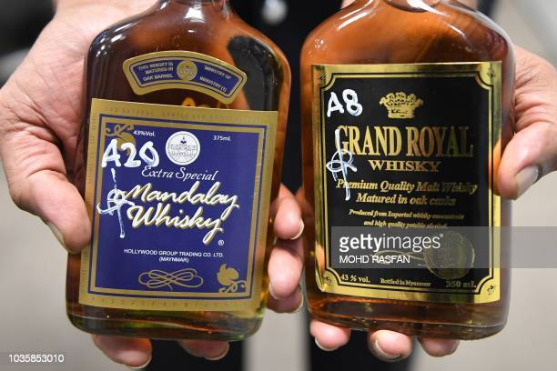 Bottles of liquor seized in police operations are displayed during a press conference by the Royal Malaysia police in Kuala Lumpur on September 19...