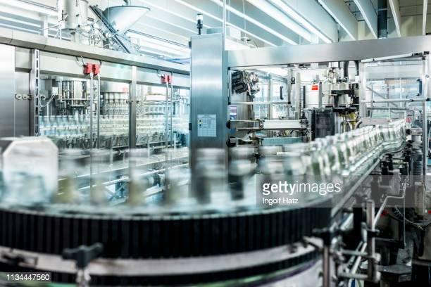 bottles of mineral water moving on conveyor belt in bottling plant - コンベヤーベルト ストックフォトと画像