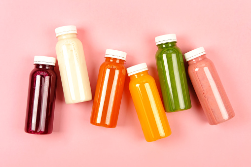 Bottles of multicolored smoothies 1034842510