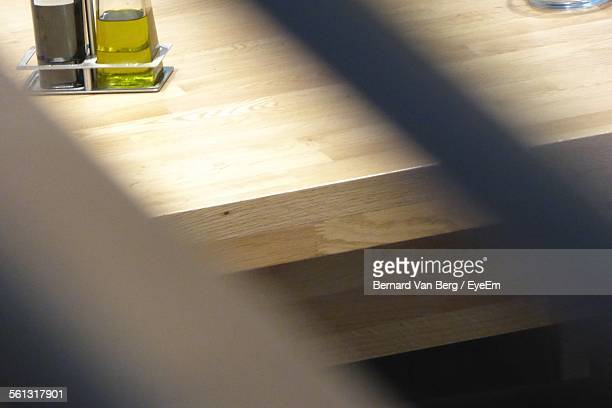 Bottles Of Oil And Vinegar On A Wooded Table In Restaurant Seen From Window