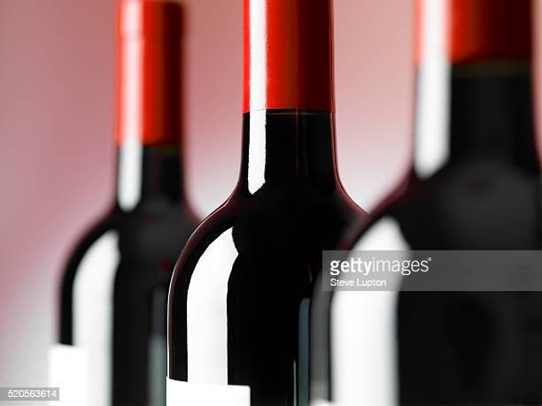 bottles of red wine - wijnfles stockfoto's en -beelden