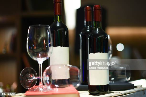 Bottles of red wine with blank front label and wineglasses