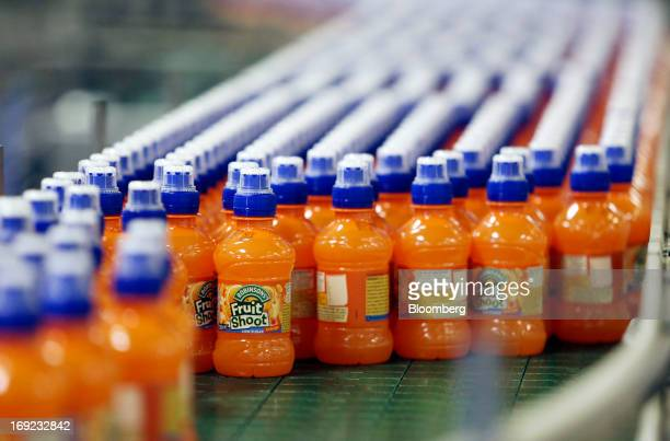 Bottles of Robinsons Fruit Shoot orange drink produced by Britvic Plc move along the production line at the company's factory in Norwich UK on...