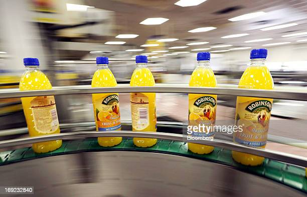 Bottles of Robinsons orange fruit and barley squash drink produced by Britvic Plc pass along the production line at the company's factory in Norwich...