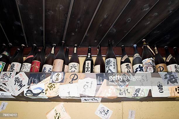 frascos de sake en una estantería en un bar - saki fotografías e imágenes de stock