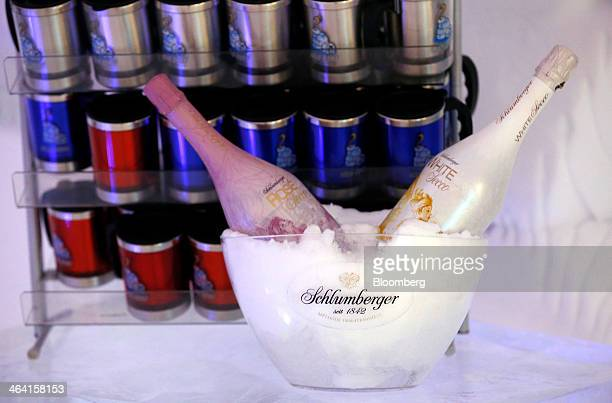 Bottles of Schlumberger white and rose sparkling wine sit in a bowl of ice at the igloo hotel operated by IgluDorf GmbH on the Parsenn mountain in...
