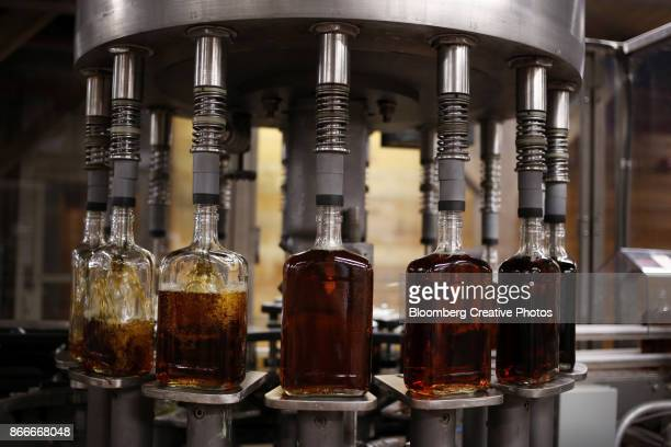 bottles of single barrel bourbon are filled on the bottling line at a distillery - distillery stock pictures, royalty-free photos & images