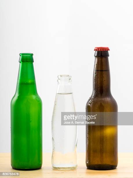 Bottles of soda, water and beer with the glass esmerilado with drops of water and a steam cloud frozen on a white bottom