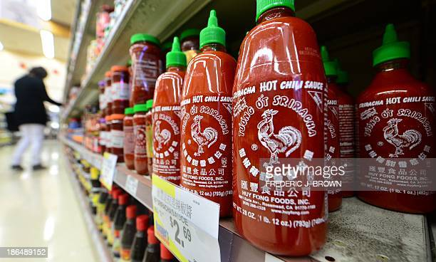 Bottles of Sriracha chili sauce are displayed on shelves as people shop inside a supermarket in Rosemead California on October 31 2013 A Los Angeles...