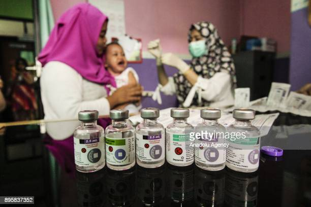 Bottles of vaccine are seen as a health officer injects outbreak response diphtheria immunization to several kids at Beji community health center...