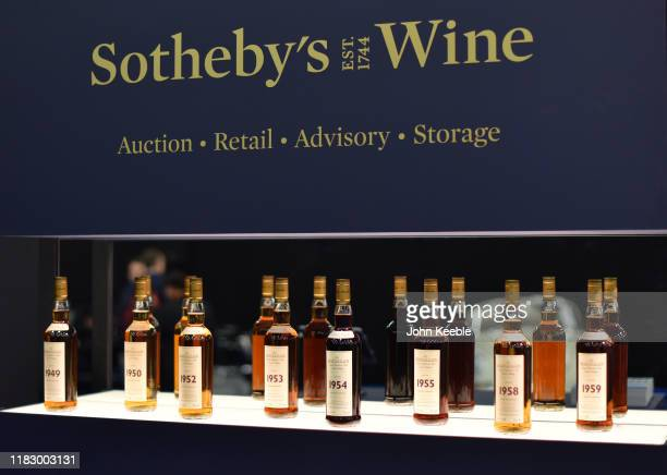 Bottles of various years old Macallan highland single malt whisky are displayed during the RM Sotherb's London European car collectors event at...