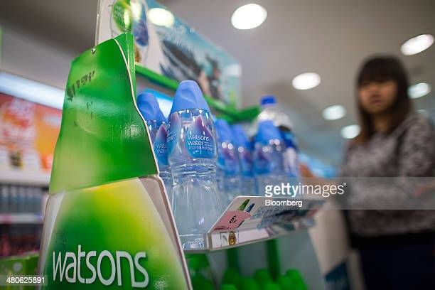 Bottles of Watsons water sit next to the cashier's counter in a Watsons store operated by AS Watson Co in the Tsim Sha Tsui district of Hong Kong...
