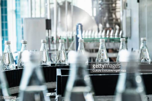 Bottles on conveyor belt in bottling facility, bottling mineral spring water