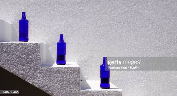 bottles on steps by wall - three objects stock pictures, royalty-free photos & images
