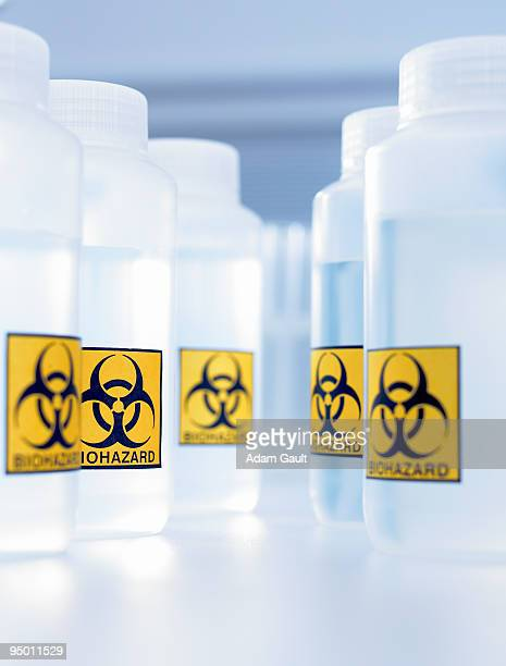 bottles with biohazard labels - biohazard symbol stock pictures, royalty-free photos & images