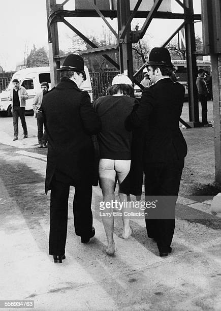 A bottomless male streaker is escorted away from Twickenham Stadium in London by two police officers during an England v Scotland match 1983