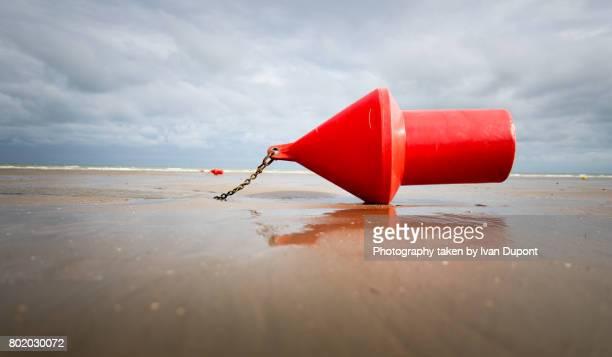 bouée rouge sur une plage à marée basse - marée stock pictures, royalty-free photos & images