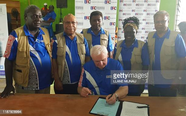 Bougainville Referendum Commission Chairman Bertie Ahern signs the referendum announcement in Bougainville on December 11 2019 Voters backing...