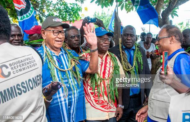 Bougainville regional president John Momis waves as he arrives at a polling station to cast his ballot in an historical independence vote in Buka on...