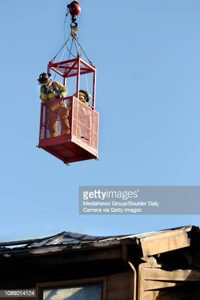 Boulder Fire Rescue Lt. Brian Eckelkamp , left, directs a crane operator as he and engineer Frank DeCoteau examine the Gold Run Condominiums building...