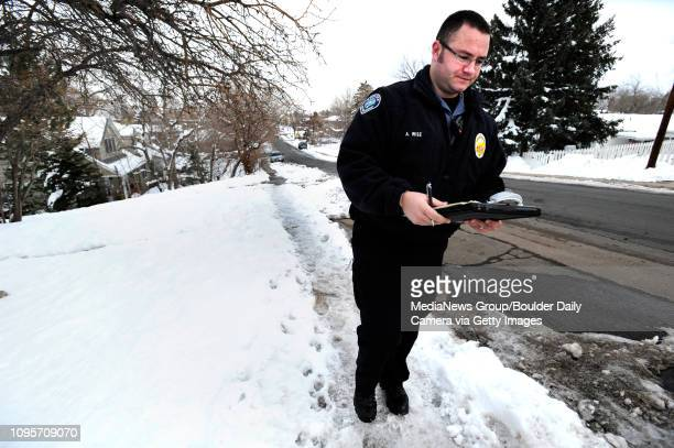 Boulder Officer Aaron Wise on Monday afternoon leaves a Notice of Violation on a house in Boulder that failed to shovel its sidewalk after last...