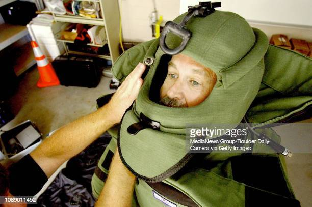 Boulder Police Officer and bomb technician Mike Pease, wears a bomb disposal suit as officer Greg Perry also a bomb technician adjusts the helmet...