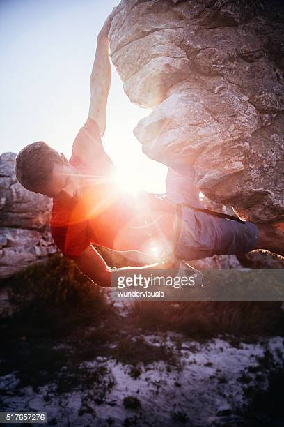 bouldering man with hand in chalk bag hanging from rock - chalk bag stock pictures, royalty-free photos & images