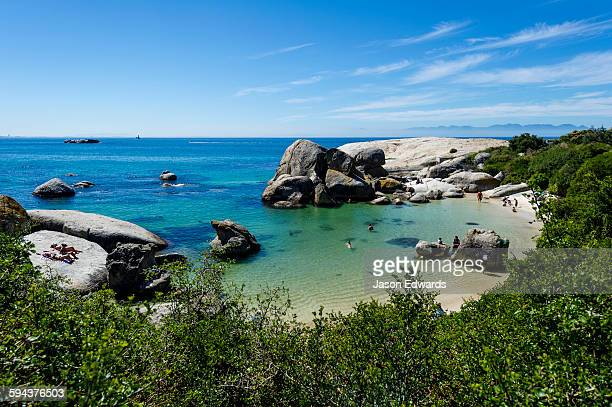 tourists swimming between boulders in the clear waters of a sheltered bay. - boulder county stock pictures, royalty-free photos & images