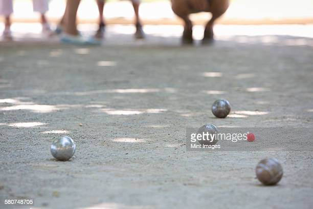 A boules game in progress on the sandy ground in the shade.