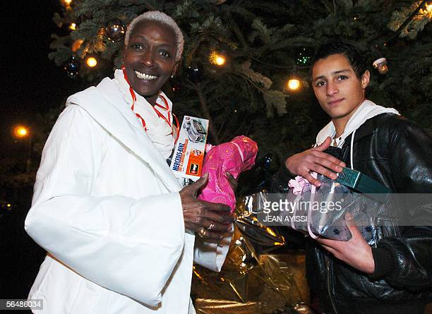 Burundian Princess Esther Kamatari poses with a child during a Christmas eve celebration for poor people 24 December 2005 in BoulogneBillancourt AFP...