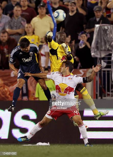 Bouna Coundoul of the New York Red Bulls punches the ball away as Carlos Mendes of the New York Red Bulls and Jay Nolly of the Vancouver Whitecaps FC...