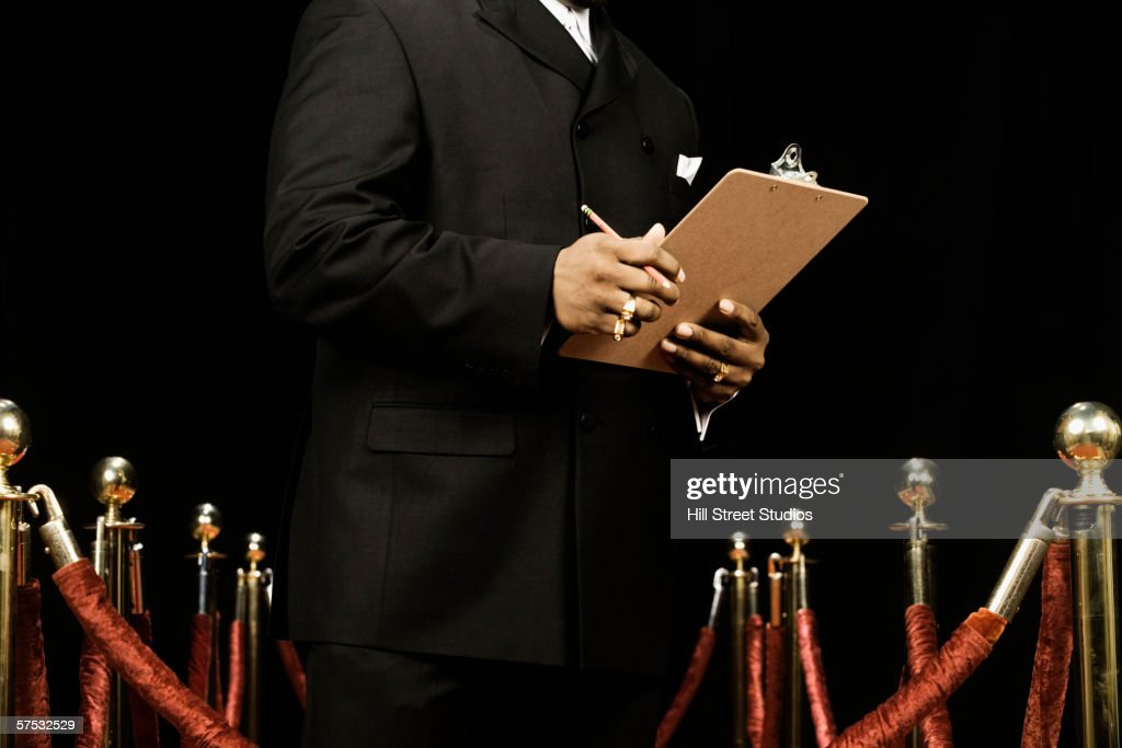 Bouncer holding a guest list : Stock Photo