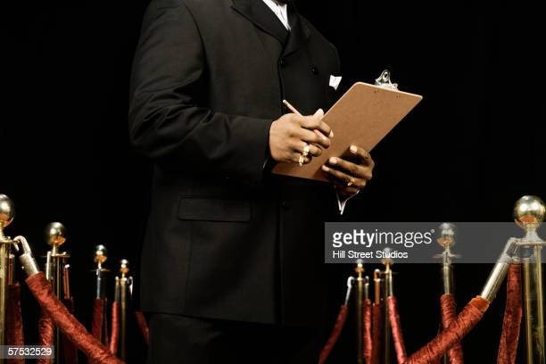 bouncer holding a guest list - bouncer security staff stock photos and pictures