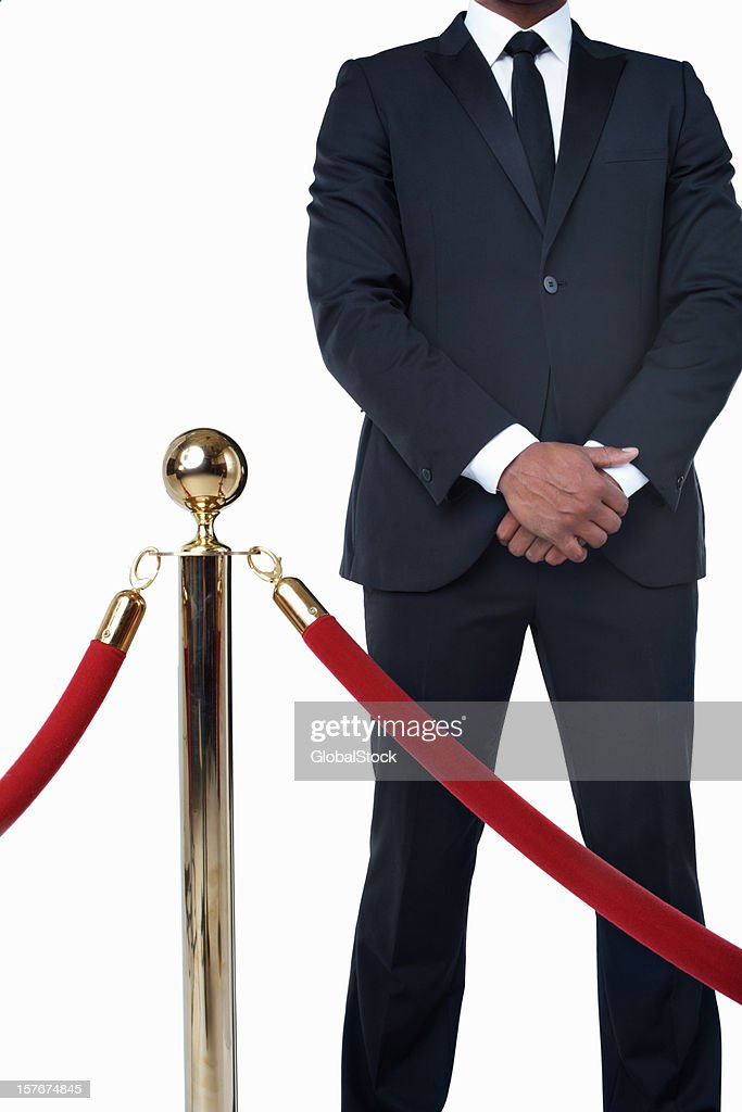 Bouncer in suit standing behind crowd control post against white : Stock Photo