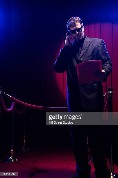 bouncer looking at guest list - bouncer security staff stock photos and pictures
