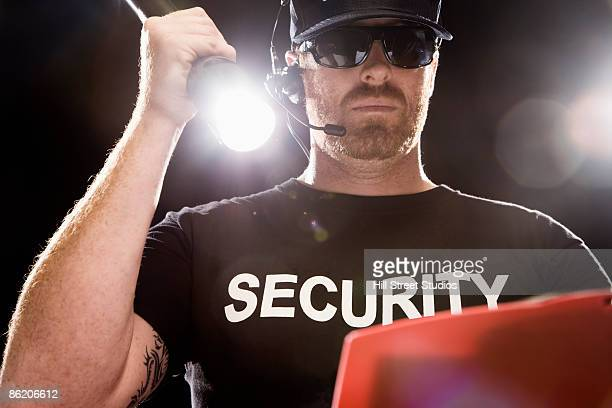 bouncer looking at guest list with flashlight - bouncer security staff stock photos and pictures