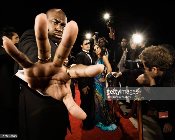 bouncer preventing entrance to a celebrity event - bouncer security staff stock photos and pictures