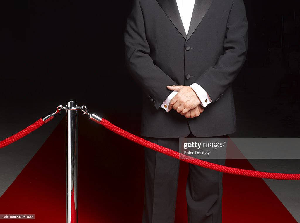 Bouncer security man standing on red carpet by ropes, mid section : Stock Photo