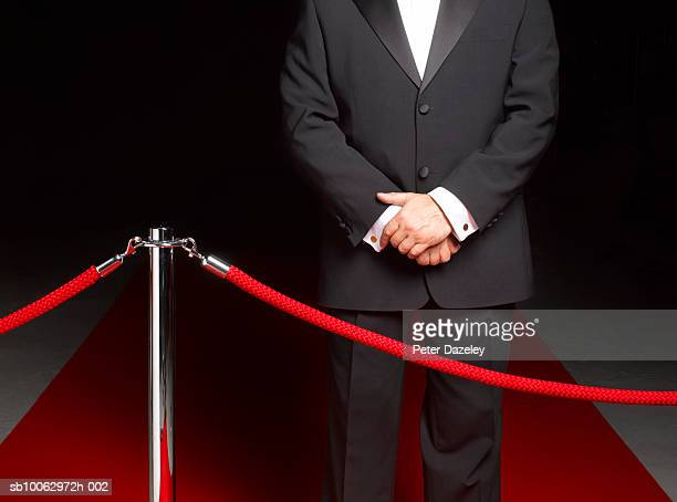 bouncer security man standing on red carpet by ropes, mid section - doorman stock photos and pictures