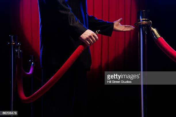 bouncer unhooking velvet rope - roped off stock photos and pictures