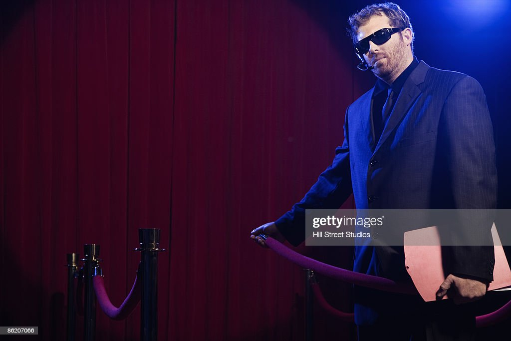 Bouncer unhooking velvet rope : Stock Photo